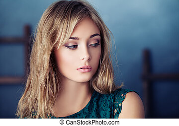 Nice woman on blue background, closeup portrait