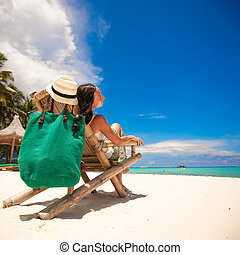 Nice woman relaxing in the wooden chair on white beach