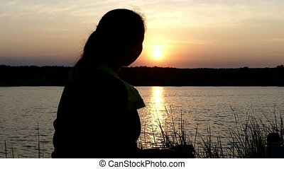 Nice woman sits on a lake bank drinking tea from a thermos