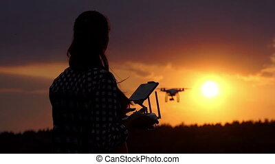 Nice woman works with a panel to control a drone at sunset