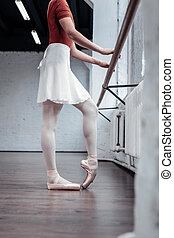 Nice young ballerina practicing near the barre