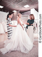 Nice young bride standing with her friend and mother -...