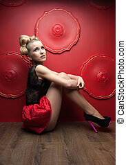 beautiful long-legged girl. sitting on the floor and hugging his legs. on the red wall background