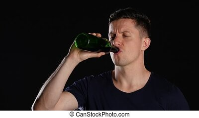 Nice young man drinking wine from the bottle. Black. Close up