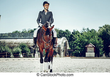 Nice young man having a ride on the horse