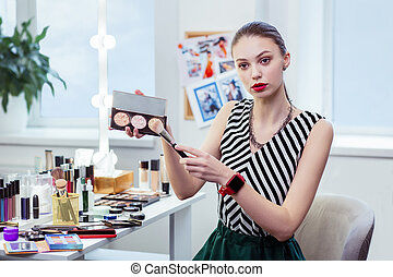 Nice young woman applying facial powder on the brush