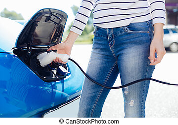 Nice young woman charging her car