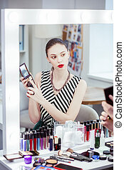 Nice young woman choosing the color for eyeshadow - Which ...