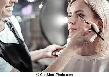 Nice young woman having her eye makeup done