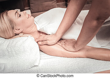 Nice young woman having her hand massaged