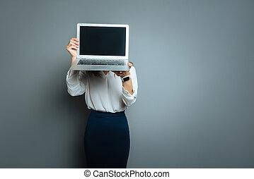Nice young woman hiding her face - Technological device....