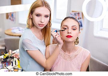 Nice young woman holding a mascara brush