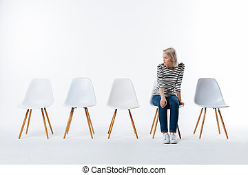 Nice young woman looking at the chair