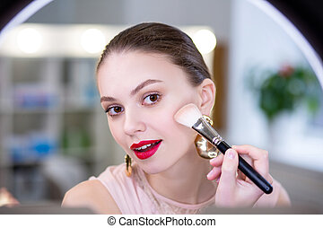 Nice young woman putting on decorative cosmetics