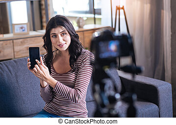 Nice young woman showing her smartphone