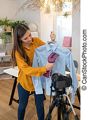 Nice young woman showing how to iron the shirt