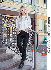 Nice young woman stands on the stairs