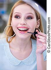 Nice young woman using a shiny lipgloss