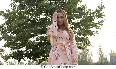 woman with loose fair hair in pink dress smiles and poses -...