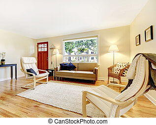 Nicely furnished living room with entryway red door and hardwood floor.
