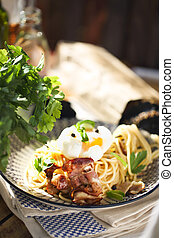 Nicely served spaghetti carbonara on black background