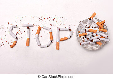 Stop smoking. Close up of broken cigarettes on ash-tray. Isolated