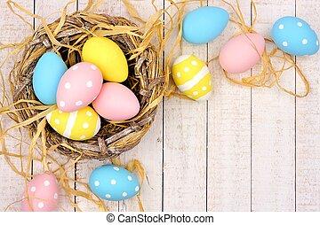 nido, esquina, frontera, con, rosa, amarillo, y, azul, huevos de pascua, contra, blanco, madera