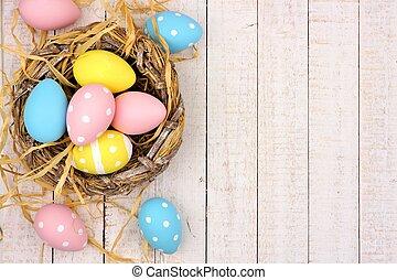 nido, lado, frontera, con, rosa, amarillo, y, azul, huevos de pascua, contra, blanco, madera