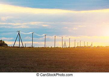 niedrig, stangen, mit, elektrisch, drähte, blank, auf, a, sonnig, sonnenuntergang, in, a, feld, von, horizon.
