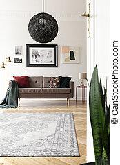 niedrige winkelsicht, von, ein, künstlerisch, wohnzimmer, inneneinrichtung, mit, a, groß, schwarz, kugelförmig, anhänger, licht, oben, a, brauner, sofa.