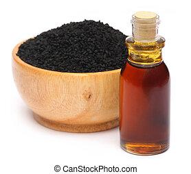 Nigella sativa or Black cumin with essential oil over white...