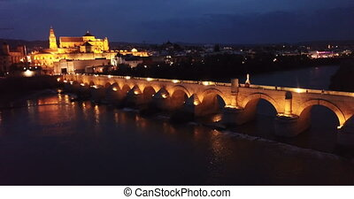 Scenic aerial view of lighted Roman bridge across Guadalquivir river and Mezquita-Catedral on background with Cordoba cityscape at twilight, Spain