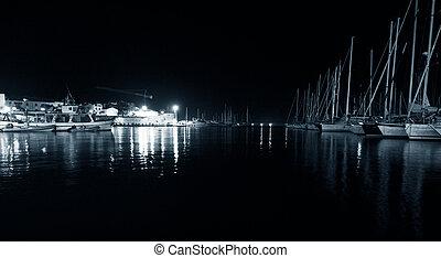 Night view Alghero from the Mediterranean Sea. Sardinia, Italy. Monochrom