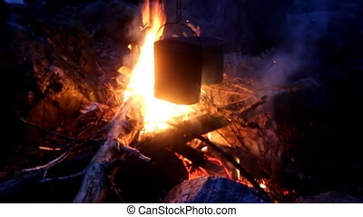Night bonfire. Dinner is cooked in pots over open fire