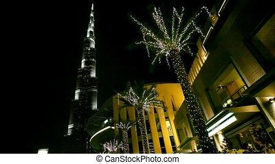 night Burj Dubai and palm-trees in Dubai, UAE.