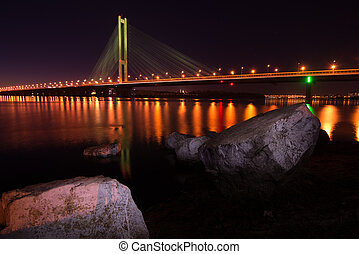 Night city. Beautiful glowing bridge over the river