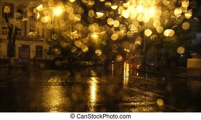 Night city in the lights of street lamps. Defocused view through a wet glass with raindrops