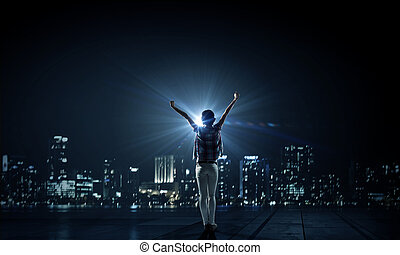 Night city life - Rear view of young woman with hands up ...