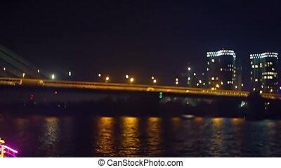 Night city lights, lively traffic on the glowing bridge