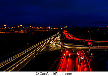 Night city road in Germany with blurred light tracks from cars