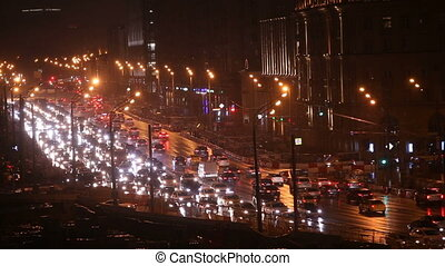 Night city road with headlights of cars moving on highway