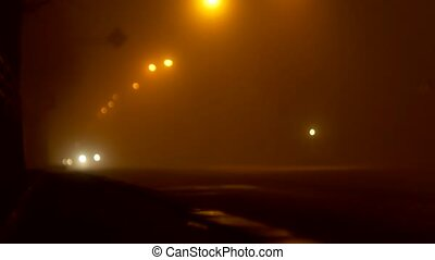 Night city street in the fog, road with cars, headlights,...