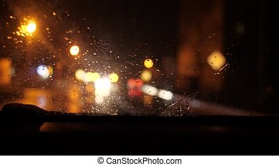 Night city through the windshield of a moving car. It is raining, lights are shining and oncoming cars are passing