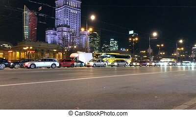 Night city traffic in the center of Warsaw near the Palace...