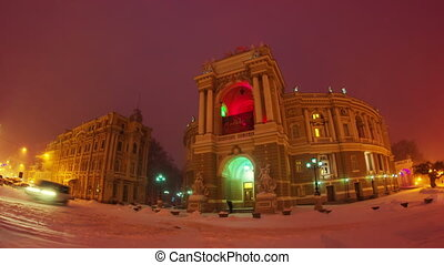 Night city traffic timelapse in snow storm near Opera House in Odessa,  4K