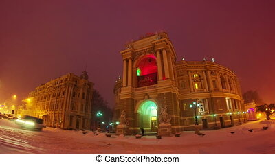 Night city traffic timelapse with zoom in snow storm near Opera House in Odessa