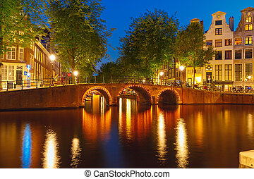Night city view of Amsterdam canal and bridge, Holland,...