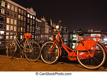 Night city view of Amsterdam canal, bridge, boats and bicycles, Holland, Netherlands.