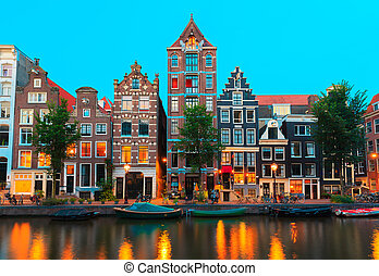 Night city view of Amsterdam canals and typical houses,...