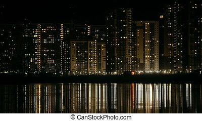night cityscape reflected in water time lapse
